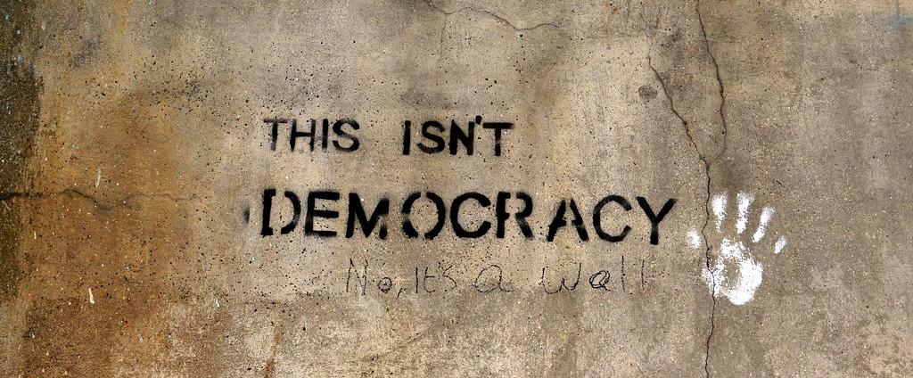 """Graffiti auf einer Wand: """"This is not democracy"""" – »Das ist keine Demokratie«"""